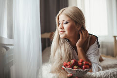 Young woman laying on bed with strawberry Royalty Free Stock Photos