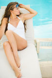 Young woman laying on chaise-longue at poolside Stock Photography