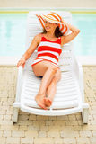 Young woman laying on chaise-longue Stock Images