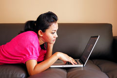 Young woman laying on a couch and using a laptop Royalty Free Stock Image