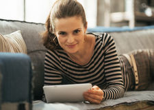 Young woman laying on couch and using tablet pc Stock Photo