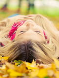 Young woman laying down in autumn park Stock Photos