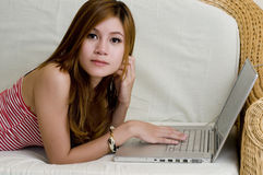 Young woman laying down with computer Royalty Free Stock Photos