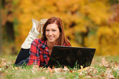 Young Woman laying down with a laptop computer Royalty Free Stock Images
