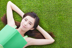 Young woman laying down  on a meadow with books Royalty Free Stock Photography