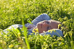 Young woman laying on field Stock Photos