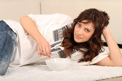 Young woman laying on the floor. Young brunette woman laying on the floor and listening to music stock photography