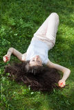 Young woman laying on grass Stock Images