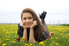 A young woman laying on the grass. With yellow dandelions around Stock Photo