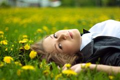 A young woman laying on the grass. With yellow dandelions around facing camera Stock Photography