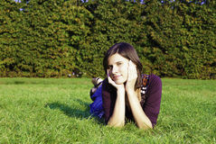 Young woman laying on green grass Stock Photography