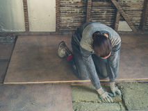 Young woman laying insulation in loft Stock Photo