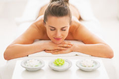 Young woman laying on massage table with candles Stock Photos