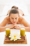 Young woman laying on massage table with candles Royalty Free Stock Photography