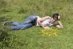 Young woman laying on a meadow close to yellow flowers in a shape of sun Royalty Free Stock Image