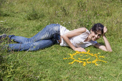 Young woman laying on a meadow close to yellow flowers in a shape of sun Stock Photos