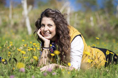 Young woman laying on a meadow with yellow flowers Stock Photo