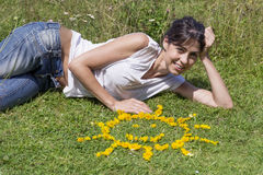 Young woman laying on a meadow with yellow flowers. Smiling woman  relaxing on a meadow with  flowers in a shape of sun Stock Image