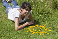 Young woman laying on a meadow with yellow flowers. Smiling woman  relaxing on a meadow with  flowers in a shape of sun Stock Photo