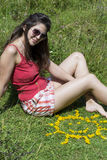 Young woman laying on a meadow with yellow flowers. Smiling woman  relaxing on a meadow with  flowers in a shape of sun Royalty Free Stock Photo