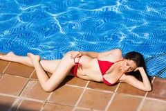 Young woman laying near swimming poo. L and smiling Royalty Free Stock Images