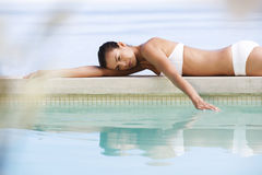 A young woman laying by a pool Royalty Free Stock Photo