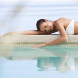 A young woman laying by a pool Stock Photos