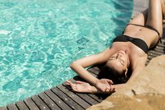 Young woman laying by the pool Stock Images