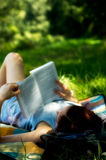 Young woman laying reading boo Stock Images