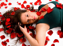 Young Woman Laying in Rose Petals Royalty Free Stock Images