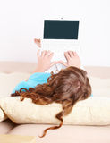 Young woman laying on sofa and using laptop. Portrait of a Young woman with head full of curls laying on sofa and using laptop in home Royalty Free Stock Photos
