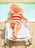 Young woman laying on sunbed with hat on head Stock Photos