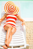 Young woman laying on sunbed with hat on head Stock Images