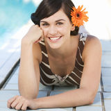 A young woman laying by a swimming pool Stock Photo