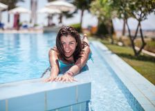 Young woman laying on the swimming pool wall Stock Image