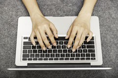 Young woman laying while using laptop Royalty Free Stock Photos