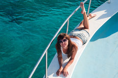 Young woman laying on yacht deck in sunglasses Stock Photography