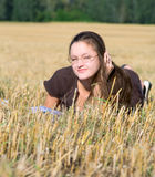 Young woman lays on yellow field Royalty Free Stock Images