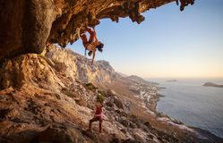 Young woman lead climbing along a roof in cave Stock Photos