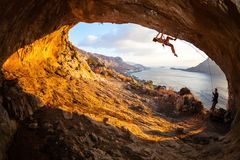 Young woman lead climbing in cave. Young women lead climbing in cave with beautiful view in background Royalty Free Stock Image