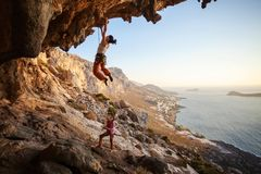 Young woman lead climbing on overhanging cliff Royalty Free Stock Photos