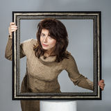 Young woman lean out from picture frame Royalty Free Stock Photo