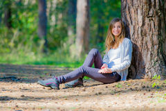 Young woman leaned back on a tree Stock Images