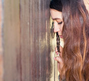 Young woman. Leaned  head to the door and grasps the handle. Wit. Girl teenager stands at the door with lowered head Royalty Free Stock Photography