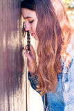 Young woman. Leaned  head to the door and grasps the handle. Wit Stock Photo