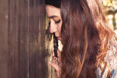 Young woman. Leaned  head to the door and grasps the handle. Wit Stock Image