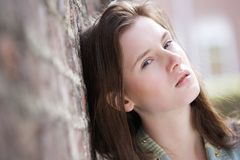 Young woman leaning against brick wall Stock Photography
