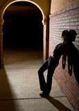 Young Woman Leaning Against Brick Wall at Night Royalty Free Stock Photography