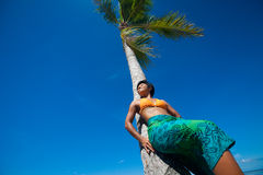 Young woman leaning against coconut tree. Beautiful young woman leaning against coconut tree on tropical beach Royalty Free Stock Images