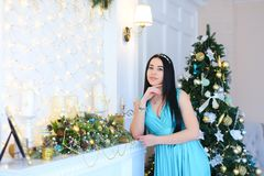 Young woman leaning against decorated fireplace, wearing blue dress and bracelet in Christmas tree background. royalty free stock images